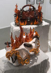 Nschotschi Haslinger Vordergrund »Brennende Tasche II«, 2018, glasierte Keramik, 32 x 38 x 27 cm ohne Sockel, Hintergrund »Brennende Tasche I, 2018, glasierte Keramik, 25 x 33 x 19 cm ohne Sockel